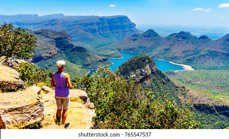 Senior woman enjoying the view of the Blyde River Canyon and Blyde River Dam from the highveld viewpoint along the Panorama Route in Mpumalanga Province of South Africa