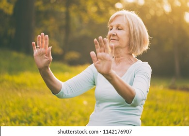 Senior woman enjoys  exercise Tai Chi in the nature.Image is intentionally toned.