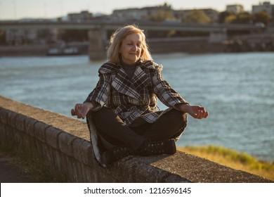 Senior woman enjoys meditating by the river.Toned image.