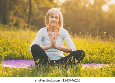 Senior woman enjoys meditating  in the nature.Image is intentionally toned.