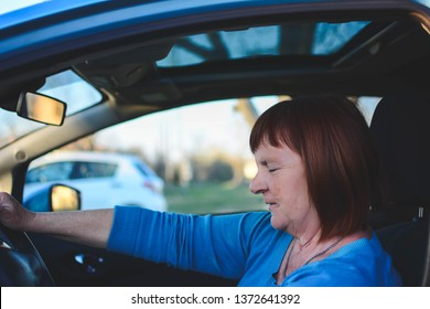 A senior woman enjoys a newly acquired car with modern systems of active and passive safety, navigation of voice commands. Panoramic roof.