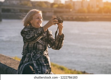 Senior woman enjoys photographing while sitting by the river.Toned image.