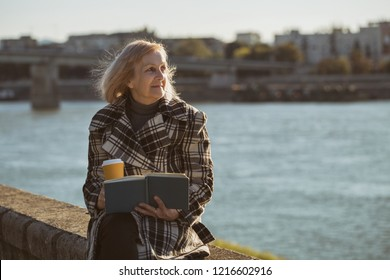 Senior woman enjoys reading book and drinking coffee while sitting by the river.Toned image.