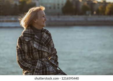 Senior woman enjoys sitting by the river.Toned image.
