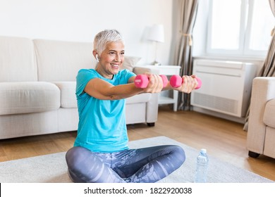 Senior woman exercise with dumbbells at home . happy mature woman doing arm workout using dumbbells. Elderly woman prefers healthy lifestyle