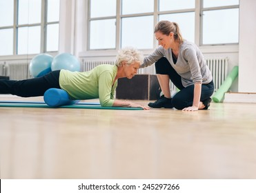Senior woman exercising with a foam roller being assisted by personal instructor at gym. Physical therapist helping elderly woman in her workout at health club.