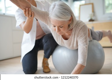 Senior woman exercising with her physiotherapist and swiss ball
