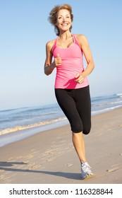 Senior Woman Exercising On Beach