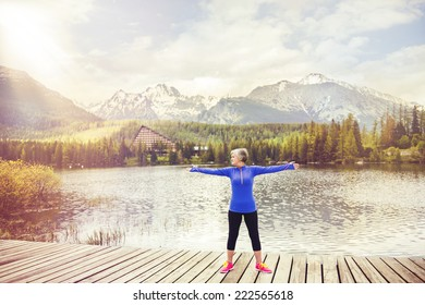Senior woman is exercising on the pier by the tarn in beautiful mountains, hills and hotel in background