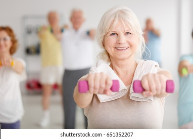 Senior woman exercising with pink dumbbells during classes