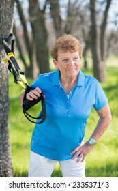 Senior woman exercising with suspension trainer in park for sport fitness