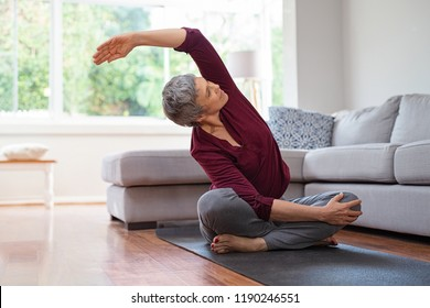 Senior woman exercising while sitting in lotus position. Active mature woman doing stretching exercise in living room at home. Fit lady stretching arms and back while sitting on yoga mat.