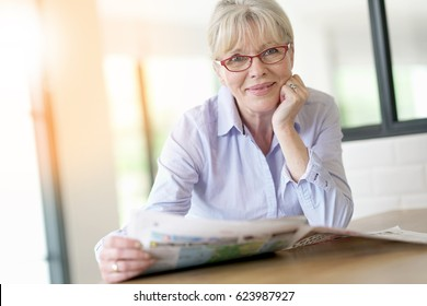 Senior woman with eyeglasses reading newspaper at home