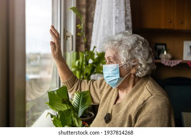 Senior woman with face mask looking out of window at home