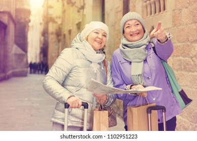 Senior woman with female friend traveling together looking for destination with city map