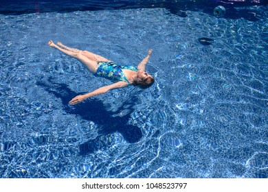 Senior woman floating in the swimming pool.