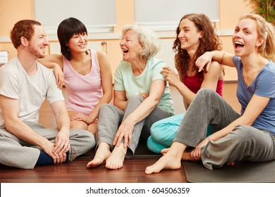 Senior woman full of vitality and group happily laughing at fitness center