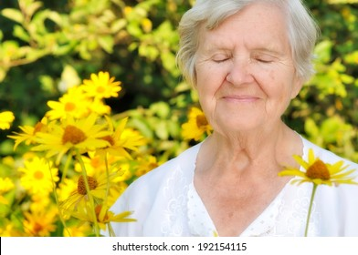 Senior woman in garden full of flowers. MANY OTHER PHOTOS FROM THIS SERIES IN MY PORTFOLIO.