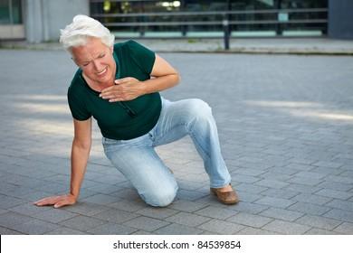 Senior woman getting heart attack in urban environment