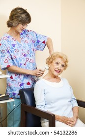 Senior woman getting ultrasound therapy for her neck pain from a chiropractic nurse.