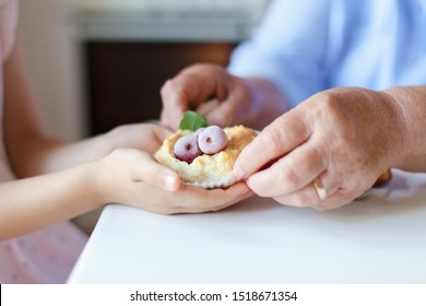 Senior woman gives homemade brioche to child girl. Family is cooking pies at home kitchen. Hands of kid and retired grandmother. Baked pastries with berries and mint leaves. Sweets with powdered sugar