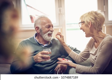 Senior woman giving her husband medication vitamins supplement.