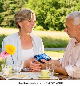 Senior woman giving husband anniversary gift in park