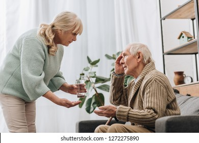 senior woman giving pills and glass of water to old man with walking stick