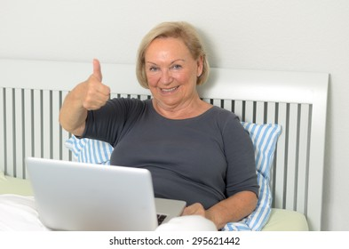 Senior woman giving a thumbs up gesture of approval as she relaxes cross-legged on her bed with her laptop computer surfing the internet