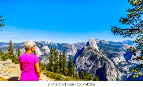 Senior Woman at Glacier Point looking at the Sierra Nevada high country, with the curved tooth of the famous Half Dome in the foreground in Yosemite National Park, California, USA