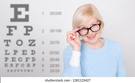 Senior woman in glasses having eye on the vision testing tables background. Visiting a doctor ophthalmologist.