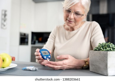 Senior woman with glucometer checking blood sugar level at home. Diabetes, health care concept
