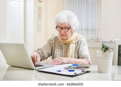 Senior woman going over financial bills with laptop at home.