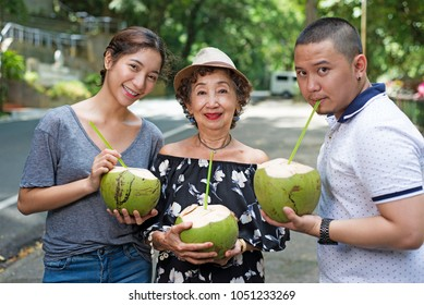 Senior woman with grandchildren enjoying fresh coconut juice. Outdoor summer picture by the roadside.