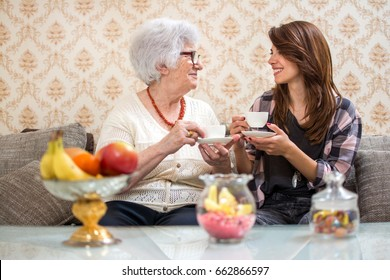 Senior woman and granddaughter drinking coffee together at home.