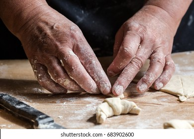 Senior woman, grandma, rolling fresh homemade croissants. Horizontal orientation. Close up on working old hands. Saturated, subdued colors