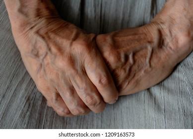 Senior woman grasps her hand