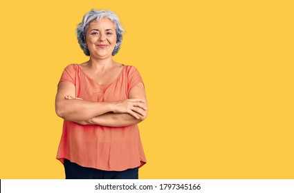 Senior woman with gray hair wearing orange tshirt happy face smiling with crossed arms looking at the camera. positive person.