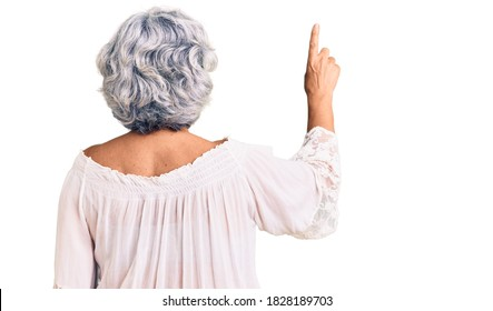 Senior woman with gray hair wearing bohemian style posing backwards pointing ahead with finger hand