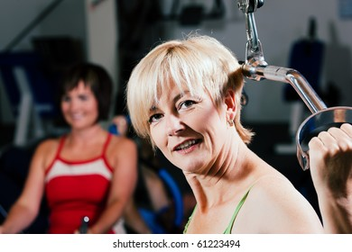 Senior woman in the gym lifting weights on a lat pull machine, exercising