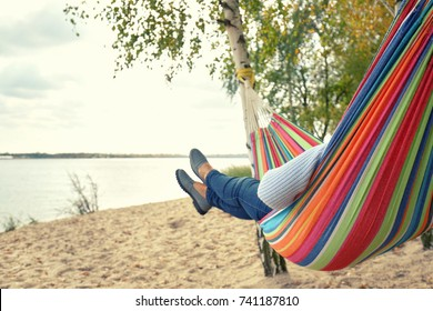 Senior woman in hammock enjoy her vacation at lake, autumn day,
