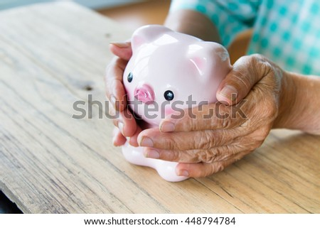 Senior woman hand covering piggy bank, metaphoric for hope, saving, retirement, pension and life insurance.
