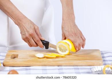 senior woman hand cutting lemon at her kitchen