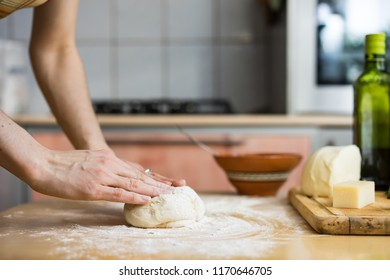 Senior woman hands knead dough on table in home kitchen