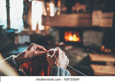 Senior woman hands knitting by the fireplace. Unrecognisable grandmother relaxes by warm fire making handmade gifts for her family. Cozy atmosphere. Winter and Christmas holidays concept.