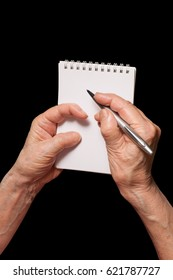 Senior woman hands with pen and blank notebook. Old person writing, calculating or making notes  theme. Isolated on black, clipping path included.