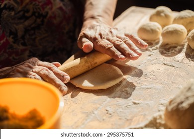 Senior woman hands rolling out dough in flour with rolling pin in her home kitchen
