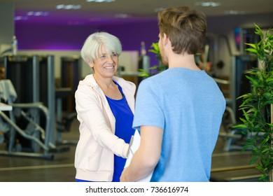 senior woman handshaking personal trainer
