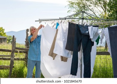 A senior woman hanging laundry on a clothesline outside to dry.