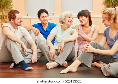 Senior woman and happy friends talking with each other at fitness studio